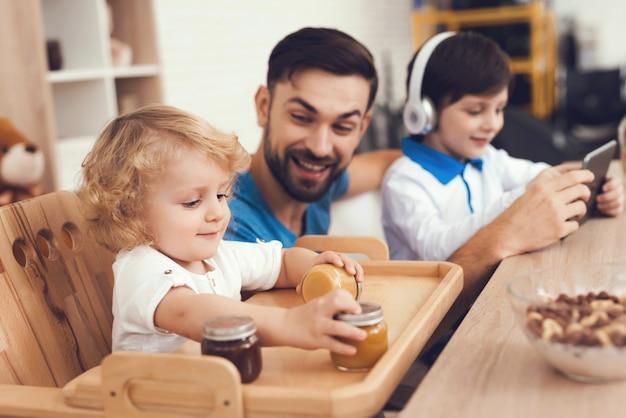 Um homem passa tempo com seus filhos em casa.