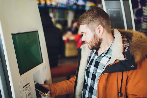 Um homem pede comida no terminal de tela de toque com menu eletrônico no restaurante de fast food.