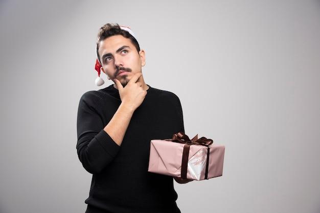 Um homem pensativo com um chapéu de papai noel segurando um presente de ano novo.