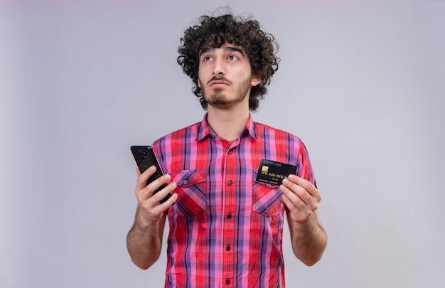 Um homem pensativo e bonito com cabelo encaracolado e camisa xadrez segurando um cartão de crédito e um telefone celular