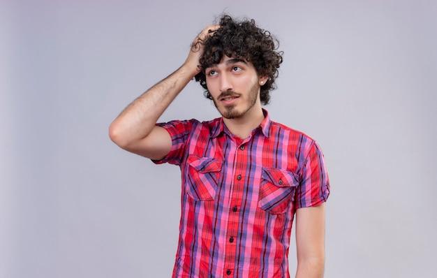 Um homem pensativo e bonito com cabelo encaracolado em uma camisa xadrez segurando a mão na cabeça