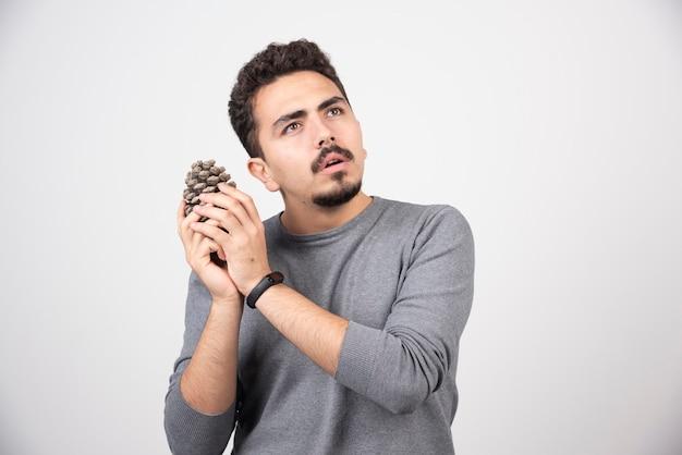 Um homem pensativo segurando nas mãos pinha.