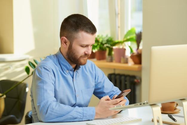 Um homem pesquisando na internet por notícias em um smartphone na frente de um laptop.