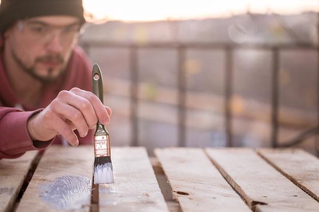 Um homem pinta com tinta branca em pranchas de madeira. homem no conceito industrial. há um lugar para o texto, o objeto está de perto.