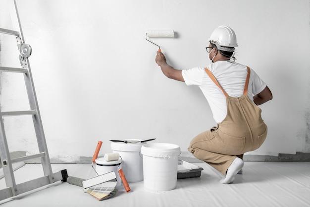 Um homem pinta uma parede branca com um rolo