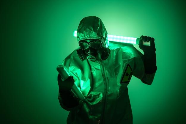 Um homem posa com uma roupa de proteção amarela com um capuz na cabeça e uma máscara de proteção contra gás, posando de pé contra um fundo verde, segurando uma lâmpada de urânio