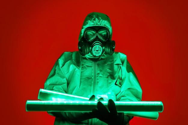 Um homem posa com uma roupa de proteção amarela com um capuz na cabeça e uma máscara de proteção contra gás, posando de pé contra um fundo vermelho, iluminando-se com lâmpadas verdes de urânio.