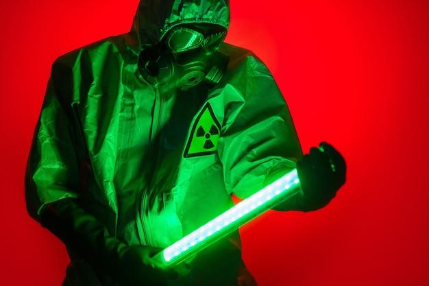 Um homem posa com uma roupa de proteção amarela com um capuz na cabeça e uma máscara de proteção contra gás, posando de pé contra um fundo vermelho, segurando uma lâmpada de urânio de luz verde nas mãos.