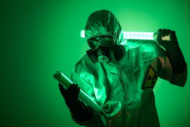 Um homem posa em traje de proteção com um capuz na cabeça, com uma máscara de gás protetora, posando em pé sobre um fundo verde, segurando uma lâmpada de urânio nas costas e a outra na frente dele