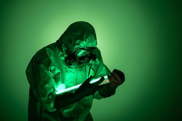 Um homem posa em um traje de proteção amarelo com um capuz na cabeça, com uma máscara de gás protetora, posando em pé contra um fundo verde, segurando lâmpadas de urânio verdes nas mãos