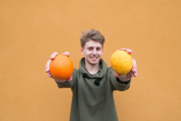 Um homem positivo com limão e laranja é isolado em uma parede laranja.