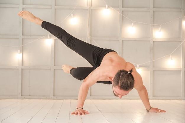 Um homem pratica ioga em um estúdio brilhante. asanas de homem e ioga com elástico.