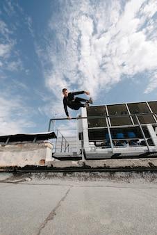 Um homem pratica parkour, corre e pula obstáculos