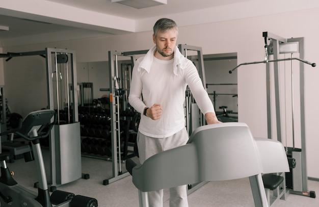 Um homem programa uma esteira antes de iniciar uma aula. treinamento cardíaco. cuidando do seu corpo. ginásio moderno