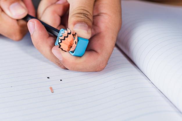 Um homem que aponta o lápis na página de livro de papel de linhas brancas