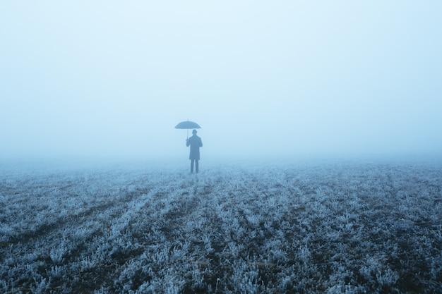 Um homem que entra em um campo com uma névoa espessa e segura um guarda-chuva. imagem conceitual