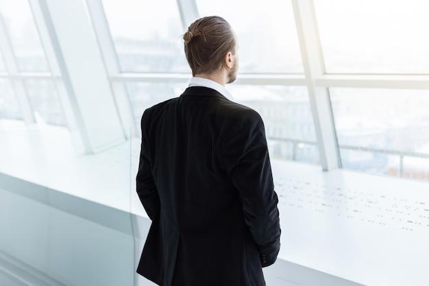 Um homem que está no interior moderno e que olha na janela.