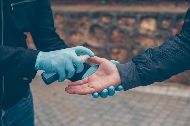 Um homem que higieniza a mão de outra pessoa em luvas no quintal durante o dia.