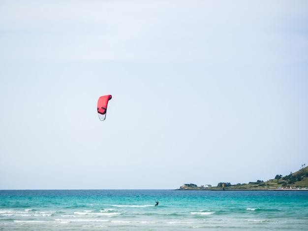 Um homem que joga o papagaio que surfa no mar. num bom dia