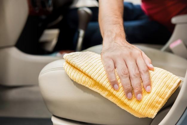 Um homem que limpa o assento de carro de couro bege com pano de microfibra