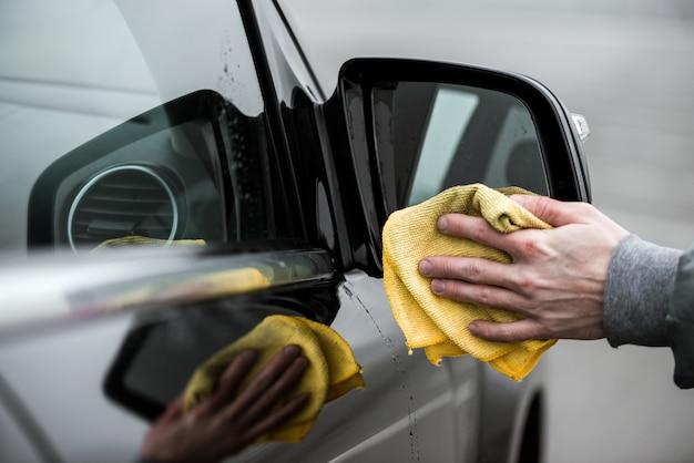 Um homem que limpa o espelho de carro com pano de microfibra, conceito de detalhamento do carro.