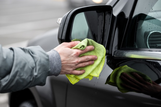 Um homem que limpa o espelho de carro esquerdo com pano de microfibra, conceito de detalhamento do carro.