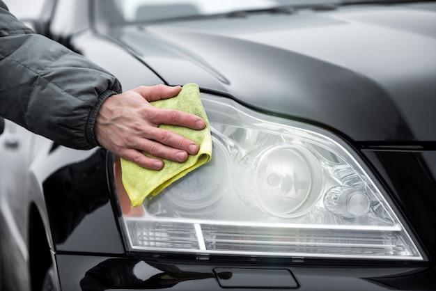 Um homem que limpa os faróis frontais do carro com pano de microfibra, conceito de detalhamento do carro.