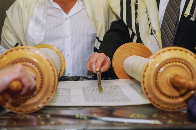 Um homem que ora com um tefilin no braço e na cabeça, segurando uma torá, enquanto lê uma oração