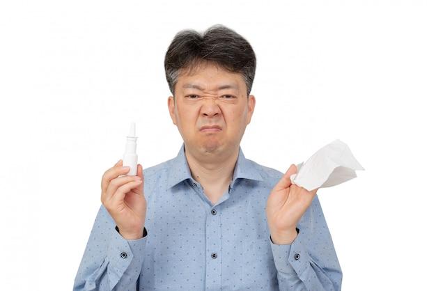 Um homem que prende um pulverizador nasal em sua mão no branco.