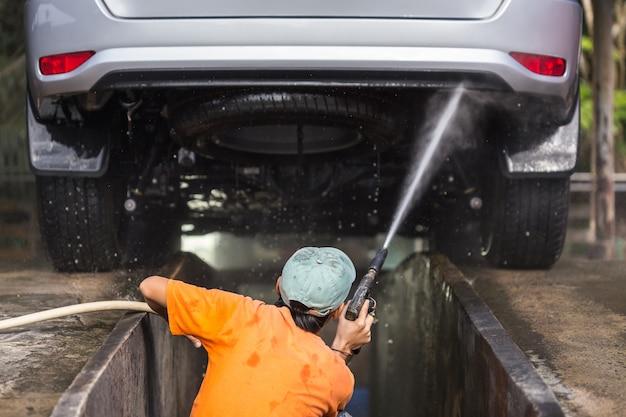 Um homem que pulveriza a arruela da pressão para a lavagem de carros na loja do cuidado de carro