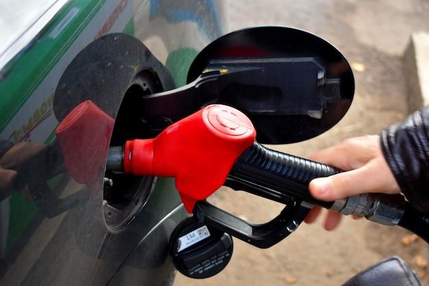Um homem que reabastece um carro com gasolina.