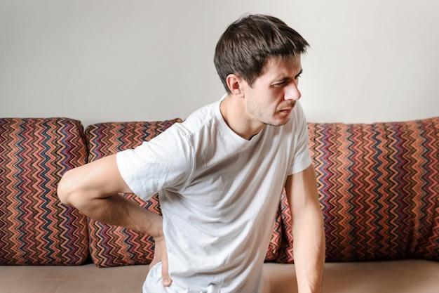 Um homem que sofre de dor nas costas em casa no sofá