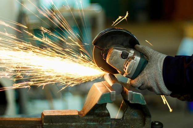 Um homem que trabalha com ferramentas manuais. mãos e faíscas close-up.