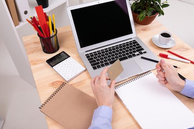 Um homem que trabalha com laptop, calculadora, canetas, lápis, cartão, telefone e uma planta em sua área de trabalho em seu escritório