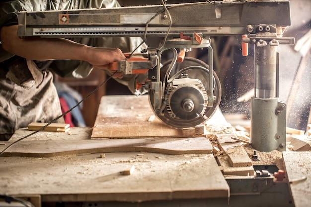 Um homem que trabalha com produtos de madeira na máquina