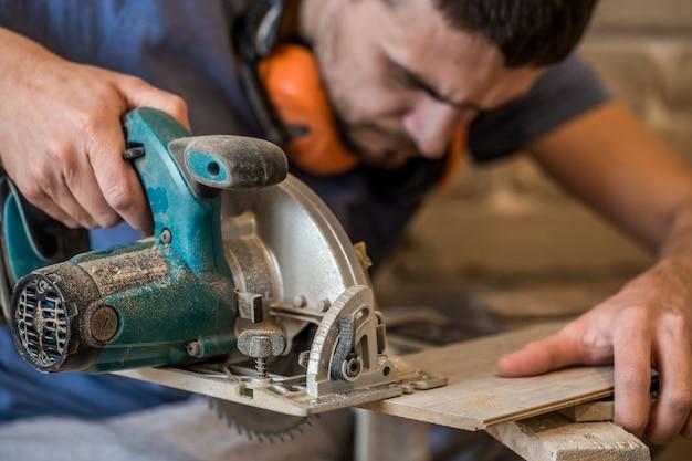 Um homem que trabalha com serra elétrica manual