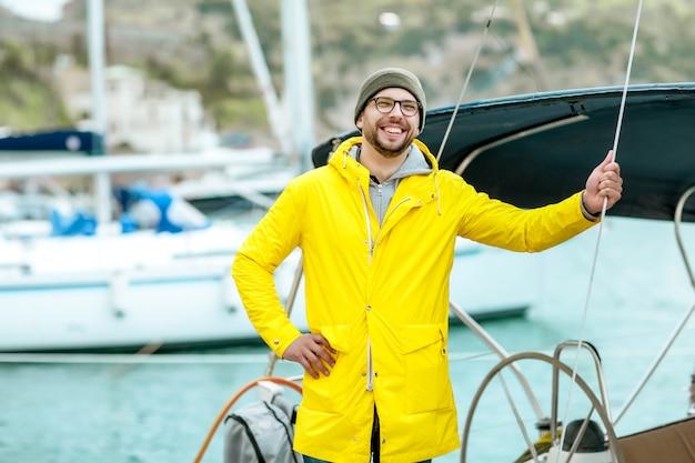 Um homem que um iate ou um marinheiro no píer fica perto de uma embarcação marítima