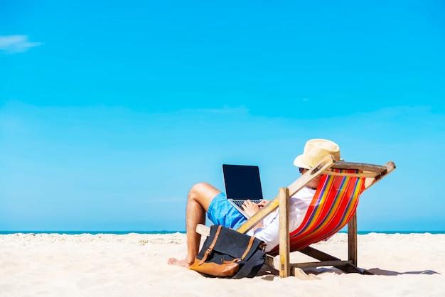 Um homem que usa o portátil na praia tropical em férias.