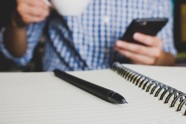 Um homem que veste uma camisa de manta azul, bebendo o café e jogando seu telefone móvel. depois de escrever o livro no escritório. pausa de trabalho