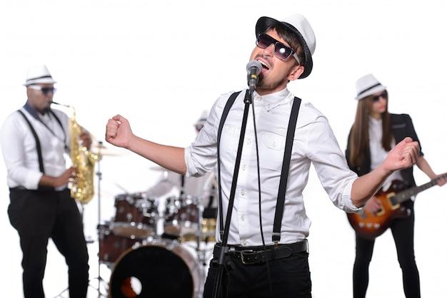 Um homem que veste vidros e um tampão canta em um microfone.