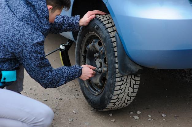 Um homem quebrou um volante em um carro e o troca sozinho na estrada.