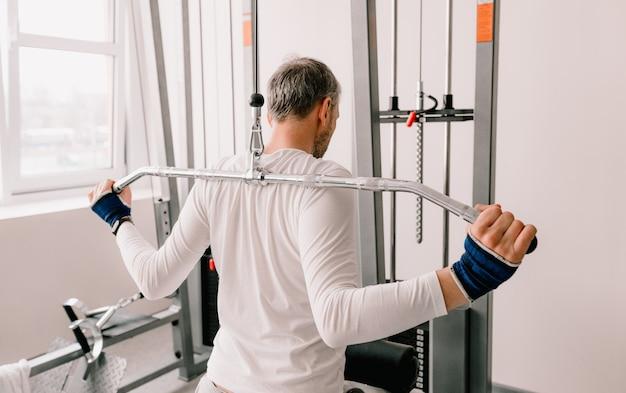 Um homem realiza exercícios no ginásio em um simulador. treinamento de volta. visão traseira