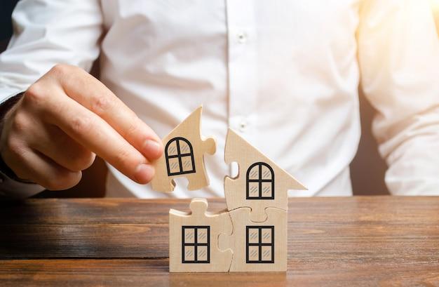 Um homem recolhe uma casa de quebra-cabeças. construção do seu próprio edifício residencial. empréstimo de hipoteca