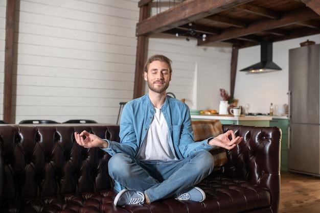 Um homem relaxado meditando sentado em seu sofá