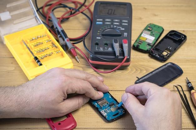 Um homem repara um telefone móvel em cima da mesa.