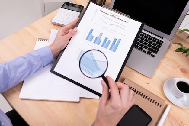 Um homem revisa os gráficos e trabalha com um laptop em sua área de trabalho com calculadora, canetas, lápis, cartão, telefone e uma planta no escritório