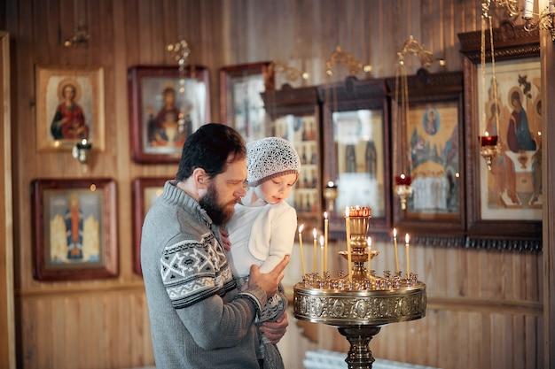 Um homem russo com barba e filha está de pé em uma igreja ortodoxa, acendendo uma vela e orando na frente do ícone.