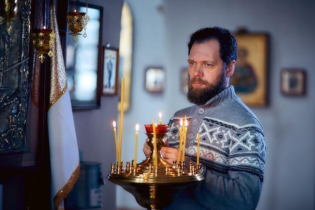 Um homem russo com barba fica em uma igreja ortodoxa, acende uma vela e reza na frente do ícone