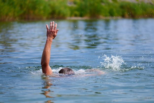 Um homem se afogando em uma lagoa. acidentes na água.