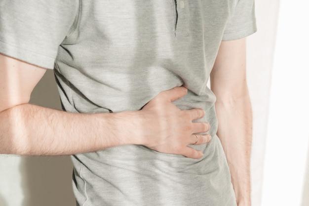Um homem se apega ao estômago com as mãos. o homem está com dor de estômago. barriga de perto